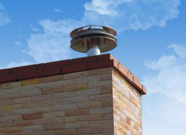 Regulator ciągu kominowego zamontowany na kominie domu